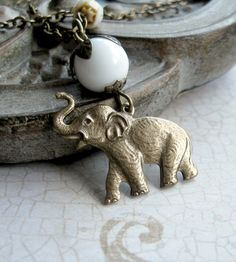 Necklace features a nicely detailed, solid brass elephant charm, which dangles from a lovely white glass bead.