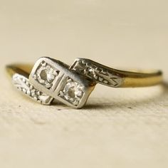 > The way this oddly asymmetric ring holds two equal diamonds. <
