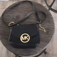 Michael Kors black crossbody Michael Kors small black crossbody. With back pocket and inside small pocket. Used several times. Inside like new! MK buckle button with some scratches/wear as shown in pictures. Michael Kors Bags Crossbody Bags