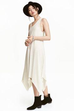 Asymetryczna sukienka: Dżersejowa rozszerzana sukienka bez rękawów. Niewykończone brzegi i asymetryczny krój u dołu.