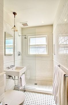 Gorgeous classic bathroom design with modern white porcelain sink with polished nickel base, white carrara marble basketweave tiles floor, glossy white subway tiles backsplash shower surround, open frameless glass shower and pendant.