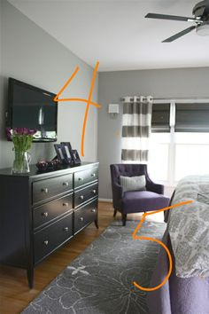 Similar layout and palette. TV mounted over large dresser opposite bed.