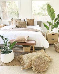 Quarto com colcha edredom branca  almofadas em tons terrosos e diferentes texturas de tecidos. Trama de sisal e fios naturais.