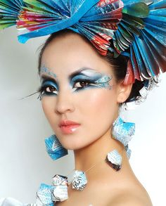 Vibrant artistic blue and black fantasy make-up accented with crystals and origami props.