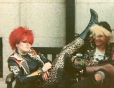 1980s: goth mix between victorian and punk. hair is short and color, printed tights/leggings, combat boots, leather jack