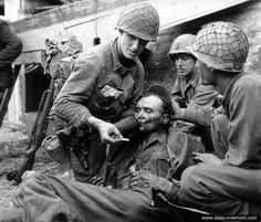 19 août 1944 : le lieutenant américain Stockridge Bacchus de la compagnie A du 314ème régiment de la 79ème division d'infanterie donne à boire à un prisonnier allemand blessé
