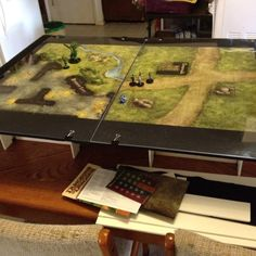 Table top gaming table made of foam board and felt with a plexiglass top. Lightweight and collapsible for portability and easy setup. Allows for a raised play area, leaving room on the actual table for rule books, game pieces, food, etc.