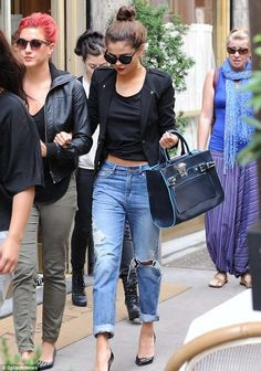 Styling with Boyfriend jeans and top knot bun. Selena kills it here..