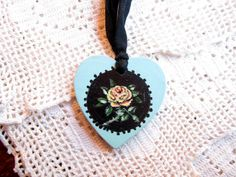 Hand painted blue heart with a yellow rose against a black circle, hung on black ribbon