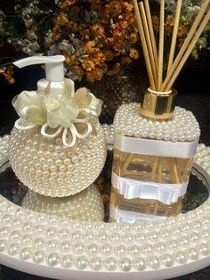 Bandeja espelhada com pérolas Medidas 33x23x5 Aromatizador de ambiente com varetas, 250 ml, frasco decorado com pérolas e fita de cetim. Acompanha 5 varetas. Sabonete líquido artesanal perfumado dourado, frasco super luxo todo em pérolas, com flores de organza e cetim. Se tiver dúvidas...