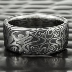 The spirit of the Samurai is strong in this 8mm wide Damascus STAR ring. An all stainless steel ring, with two sinuous four pointed stars on either side, it is powerful to behold. The addition of our dark Fire Oxide, highlights the flowing grain of the pattern that connects the stars, and energizes the design further. Big, bold, and masculine the STAR design opens a door into the legendary past of the sword maker's art.