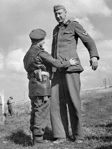 Tallest German surrenders to short soldier in World War Two picture