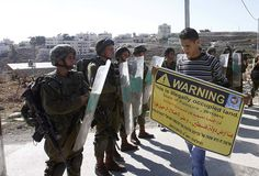 A Palestinian protester holds a placard in front of Israeli soldiers during a demonstration in the West Bank village of al-Masara near Bethlehem, marking the recognition of a sovereign Palestinian state by the United Nations. Gaza Strip, Israel News, United Nations, North Africa, Palestine, Obama, The Voice, Insight, The Neighbourhood