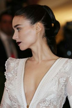 Rooney Mara pairs a a blackened-plum lip with a lacquered, sculptural updo at the punk-themed Met Gala, 2013