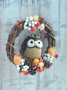 Needle felted owl on dry flower wreath ornament This listing is for an owl prince resting on a flower wreath. The owl prince is made of wool using needle felting technique. The wreath is made of dried seeds and pine cones and artificial berries. The owl is firmly attached on the flower wreath. Dimensions of the wreath : 10cm in diameter Dimensions of the bird : 5.5cm in height This item is READY TO SHIP Every item is handmade by me with great care and love. If you are interested in other...