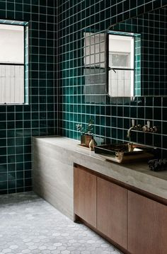 INSPIRATION: the bathroom's rich forest green tiling pair effortlessly with timber cabinetry and brass fittings | est living