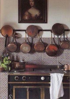 Tiled workspace, hanging copper pans, antique stove w. brass trim
