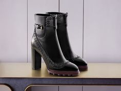 High heeled ankle boots in polished calfskin with decorative incisions, ankle strap, and contrasting soles.