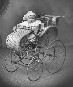 Baby seated in a wicker pram, c. 1900's.