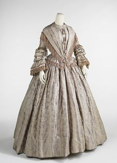 Afternoon dress, c 1848. Fashionable dress of the 1840s was inspired by Queen Victoria (1819-1901) who was crowned in 1838. Due to her modesty and youth she favored styles which were reserved as befitted a young queen. The elongated bodice and wide V-shape over the bust were essential parts of this decade and can be seen in this example. The addition of many textures from the textile pattern, fringe, tassels, and fabric manipulation through pleating, shirring and puffing, give the dress