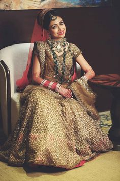 gold bridal lehenga, green necklace, contrast jewellery, double dupatta, contrast dupatta, red dupatta on head with gold lehenga, green jewellery with gold lehenga, red choora, layered jewellery. short sleeved blouse