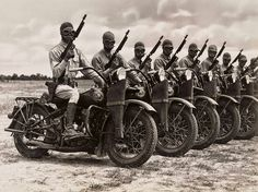 U.S. soldiers on Harley-Davidson WLA motorcycles, equipped with unloaded Thompson submachine guns during WWII