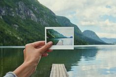 Hand holding up polaroid instant photo of beautiful lake jetty n by Aila Images for Stocksy United