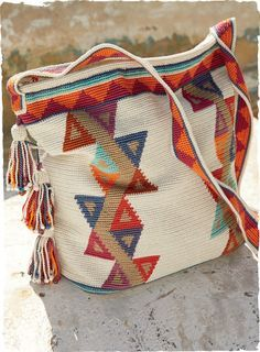 Die aufwendig handgehäkelte Tragetasche aus Pimabaumwolle schmückt ein Mosaik aus Dreiecken und Zickzackstreifen. Mit Schultergurt, Reißverschluss oben und seitlichen, perlenbesetzten Troddeln.