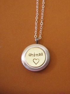 """""""Ahimsa"""" is a term meaning to do no harm.... the avoidance of violence.   Sterling silver locket with a recycled brass center hand stamped Ahimsa with a heart Holds two 16 mm round photos.   Comes with a 2.2 mm sterling silver flat cable chain and is 16 inch length. Due to the handmade nature this may vary slightly from image"""