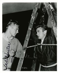 "TAB HUNTER & JAMES DEAN; Vintage candid Warner Bros. studio photo of Tab Hunter and James Dean on the set of Rebel Without a Cause, signed by Hunter. According to Hunter ""...Jimmy and I hung around outside while the crew prepped another setup. An enterprising studio publicity photographer saw us chatting and began snapping dozens of pictures—the polar opposites of America's youth culture, captured together."""