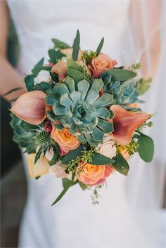 Coral & green brides bouquet featuring calla lilies, roses & succulents.