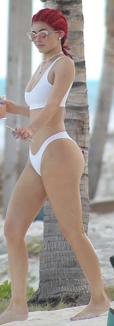 Kylie Jenner: Bikini – Nicole x Naked Wardrobe  Sunglasses – Zanzan  Necklace- Luv AJ