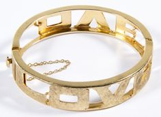 Lot 133: 14k Gold Hinged Bangle Bracelet; Having the word LOVE on each side; marked 14k on clasp