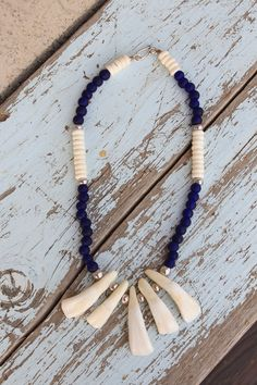 Genuine buffalo teeth necklace. Made with sinew - to be legit at rendezvous. Large silver beads in between the teeth, with white bone beads and dark blue padre beads at the top. Beautiful necklace.  $20