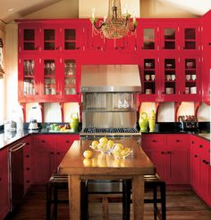 Red kitchen... I had red cupboards in our first apartment.  I repainted them only because the kitchen was the size of a small closet (as was the entire apartment).  This is beautiful and I would not change the colour of these cupboards!