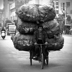 The Face Of China  - Waste Not    This is a common site across China. Men hauling seemingly impossible loads on these tricycle, trishaw, trickshaw things. This fellow is on his way to the recycling center with large bags he's filled with plastic bottles. This is not even close to the largest load I've seen being dragged about Liuzhou. Taken in front of the Liuzhou Train Station near my first apartment in China.  by Michael Steverson via flickr