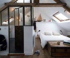 Dans cette chambre adulte sous les toits, la salle de bain se cloisonne derrière une verrière tendance.