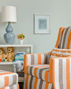 Adorable grey and orange nursery design with pale blue walls paint color and glossy white lacquer console table bookcase filled with blue double gourd lamp, stuffed animals and books. Orange and gray striped swoop arm nursery glider with matching ottoman paired with white and orange dragonfly pillow.