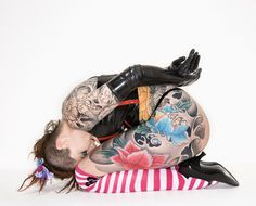 Adult caucasian woman with tattoos sitting on floor.