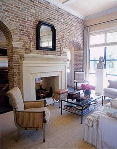 I love featuring a brick wall in interior living space, it adds a rustic quality. This family room is decorated using neutrals & the brick wall serves as a partion between spaces, the double-sided fireplace is a beautiful feature framed with arched open brick openings on each side. Beautifully designed.