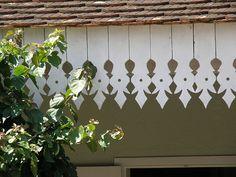 """Lambrequins, foto de C. A. P. Parchen:  """"Lindos lambrequins de uma casa estilo colonial polonês, com suas telhas planas de barro cozido, em camadas sucessivas. Os lambrequins são oriundos de regiões da Europa com neve, e visavam facilitar o gotejamento da neve que derretia do telhado. No Brasil, teve função meramente ornamental, sendo encontrados no Sul do país. São recortados em madeira, de forma artesanal."""""""