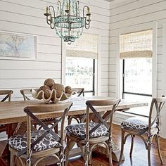 Coastal dining room with beaded-glass chandelier, shiplap walls, wooden floors, and framed nautical print. #home #decor