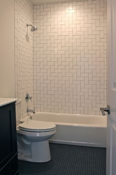 Bathroom with herringbone pattern white subway tile surround and black hexagon tile flooring.
