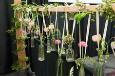 Great wedding idea! Hang flower vases from a post or fence with ribbon and vintage bottles. So fun and elegant! From Thread of Scarlet Floral Design.