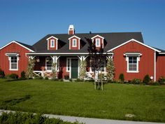 Classic red barn-inspired walls, bright white trim and a black roof all combine to create a quintessential farmhouse.