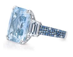 Cushion-cut 17.56 carat pale blue sapphire with two trapezoid diamond side stones of 2.41 carats. Micro-set band with 142 white diamonds and 82 blue sapphires, set in platinum.