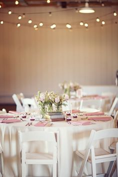 Reception tables adorned in blush pink linens, vintage books and creamy lace.