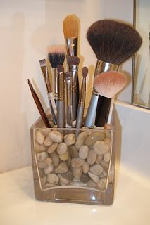 Makeup brush storage in attractive glass container filled with polished stones or glass marbles