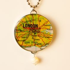 "London 1 - This map is cut out by hand and carefully placed in the silver plated setting. We then pour epoxy resin over it and allow it to harden and dry so it is protected from the elements. The setting and 21"" chain are made in the USA. The bead is glass. You can also use this as a keyring, tree ornament, zipper pull, purse, backpack or rear view mirror charm. A large split ring will be included at no charge."