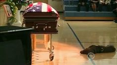 Hawkeye, a chocolate lab, lays close to his master, a fallen Navy Seal one last time. Beyond moving!  Precious!!!